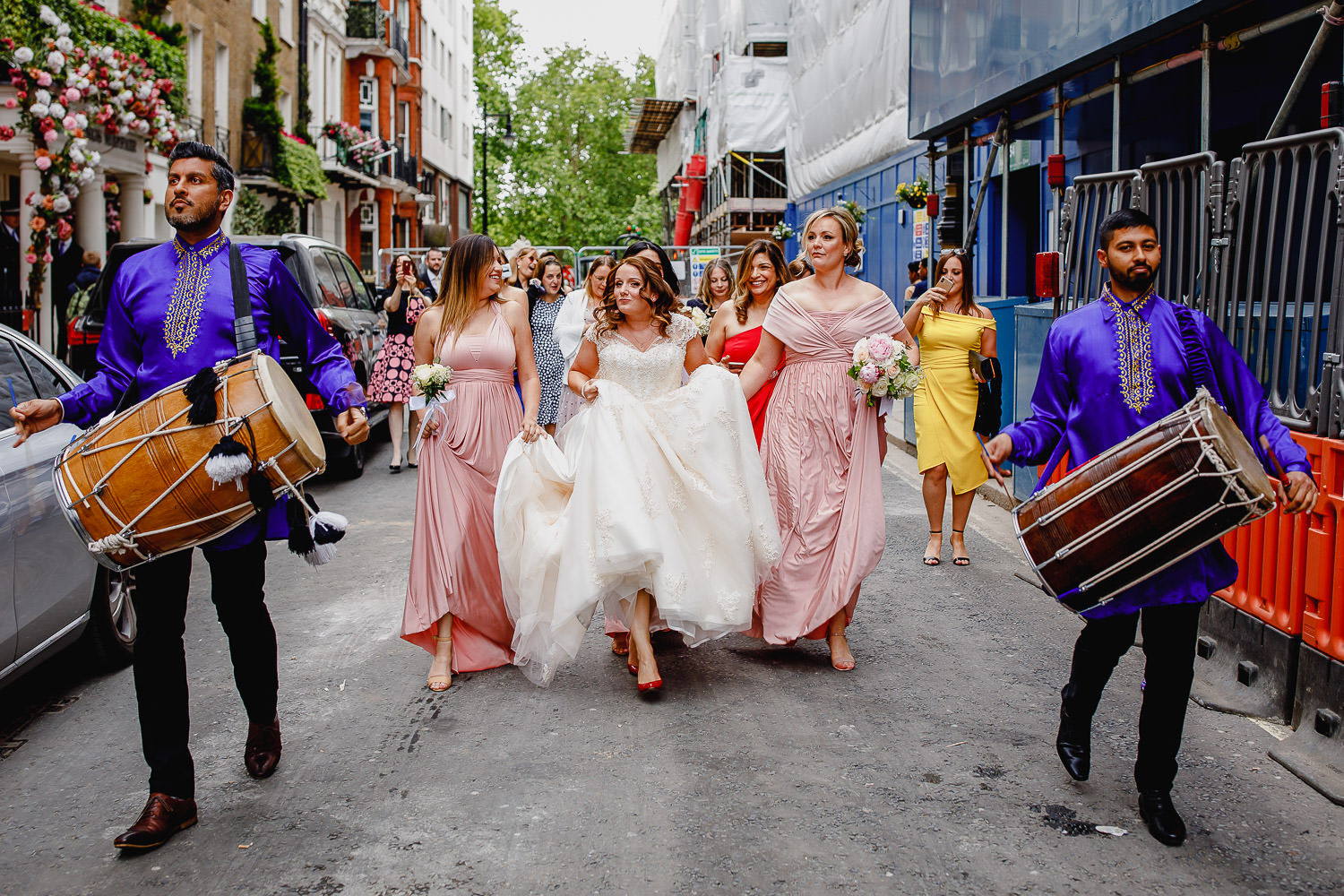Bride is escorted by her bridesmaids and drummers.