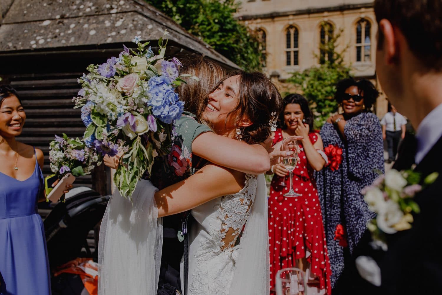 Bride hugs her guests with bouquet in hand.