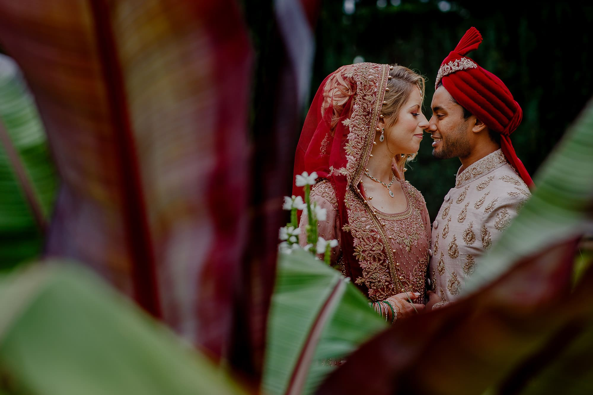 Asian and English wedding couple in vibrant sira outfit.