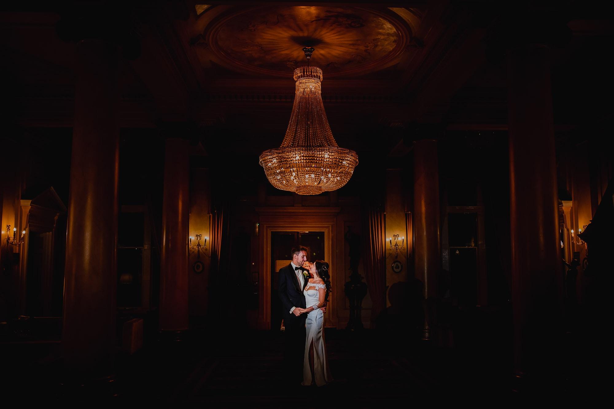 Couples wedding portrait under golden chandelier.