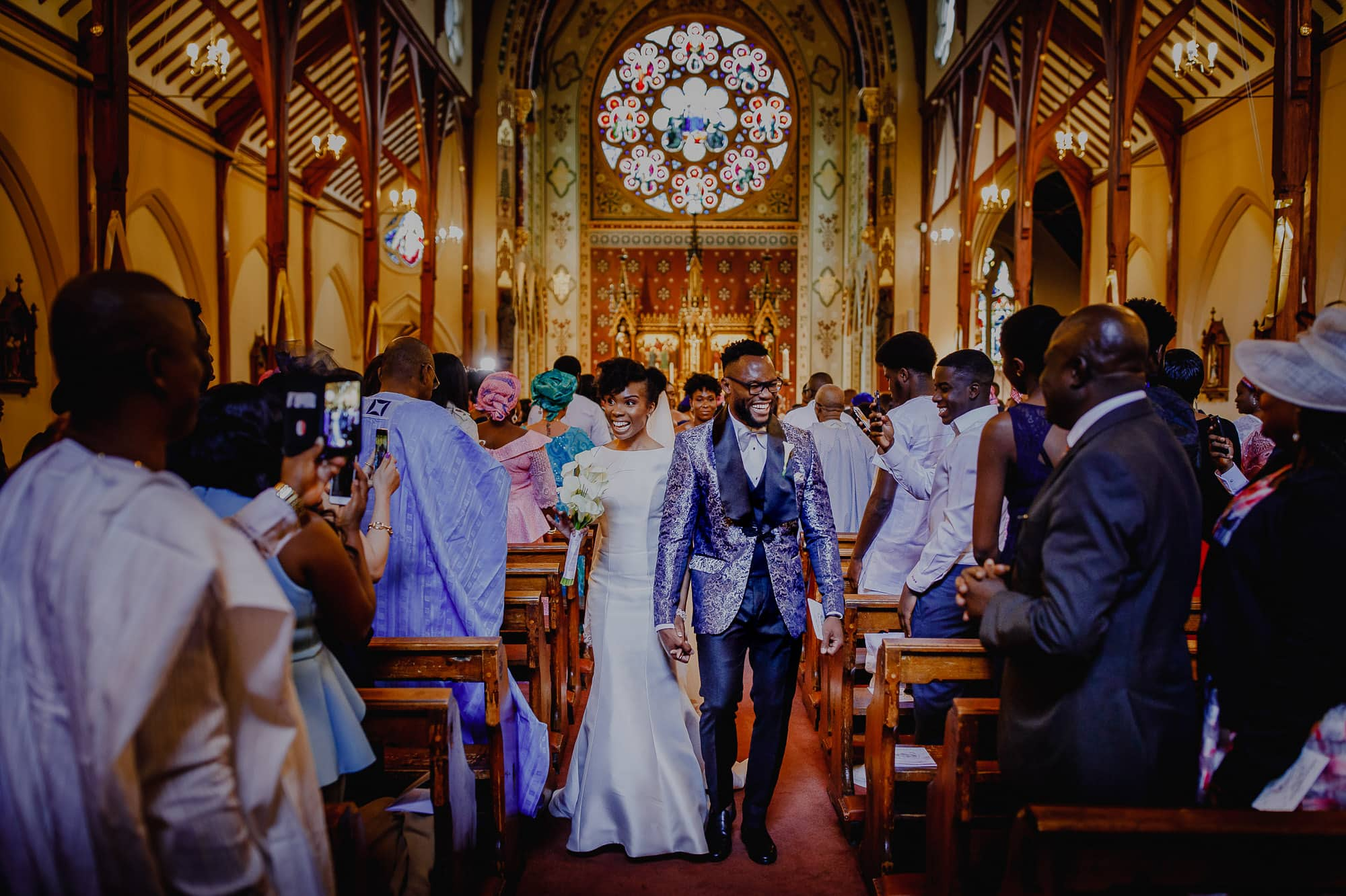 Couple walking down the aisle as they exit the church.